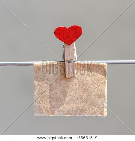 Note on kraft paper with a pin in the shape of heart