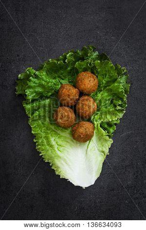 Healthy vegetarian falafels on black slate background