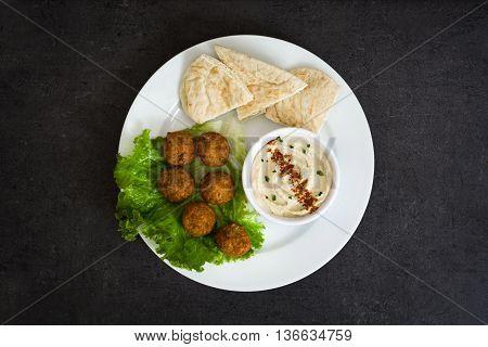 Vegetarian falafels, hummus and pita bread on slate background