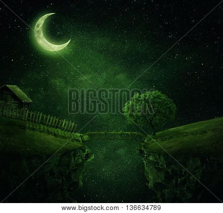 Country image with a wood bridge connecting two hills. Idyllic view of a old cabin with fence and a tree near the cliff in a starry magic night
