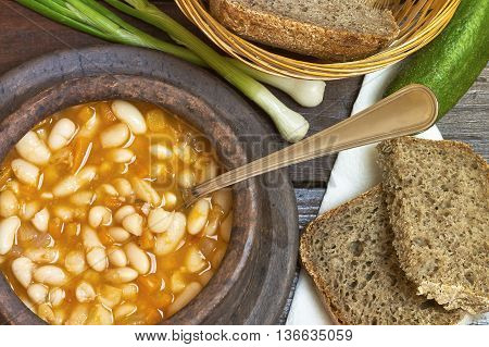 Cooked beans in clay bowl served with whole wheat bread and scallion on dark wooden background. Top view