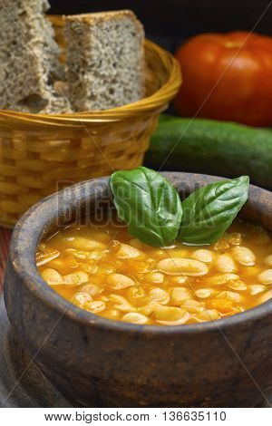Cooked beans in clay bowl served with whole wheat bread and basil leaves