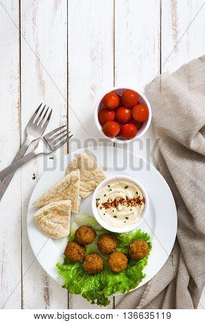 Vegetarian falafels, hummus and pita bread on white wooden background