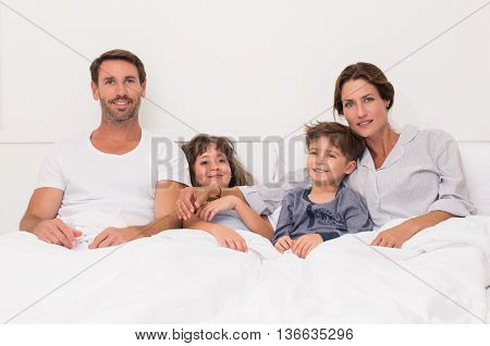 Parents and children smiling and looking at camera on bed. Portrait of a happy family sitting on bed in the morning time. Portrait of a happy family watching television before going to bed.
