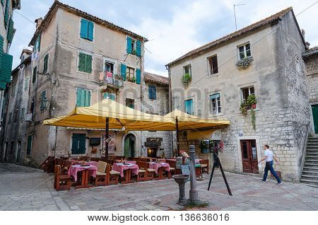 KOTOR MONTENEGRO - SEPTEMBER 21 2015: Unidentified people are at square in Old Town of Kotor near outdoor cafe Montenegro