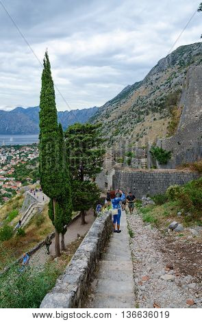 KOTOR MONTENEGRO - SEPTEMBER 21 2015: Unidentified tourists climb on stone steps to ancient fortress walls above city of Kotor and Bay of Kotor Montenegro