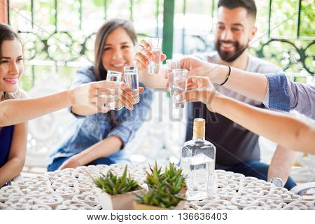 Five friends raising their glasses and making a toast with tequila shots during a party outdoors