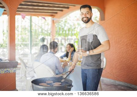 Happy Guy Cooking Burgers In A Grill Outdoors