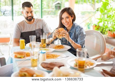 Gorgeous young Hispanic woman eating a hamburger with her boyfriend during a friend reunion outdoors