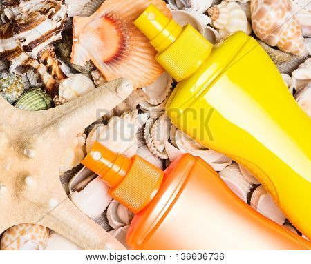 Cosmetic sunscreen products with variety of shells and starfish. Concept of skin care cosmetics containing sun protection factor