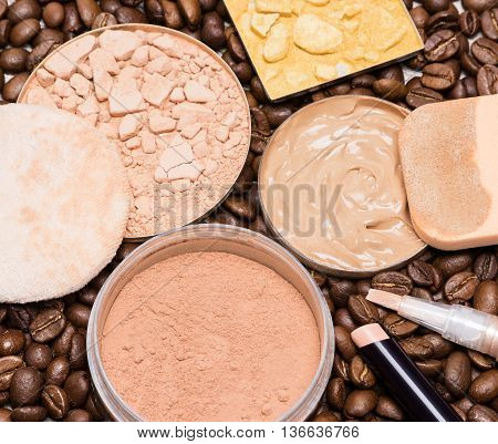 Concealers, liquid foundation, open jar of loose cosmetic powder, crushed compact and shimmer powder golden color on coffee beans. Makeup products to create the perfect skin tone and complexion