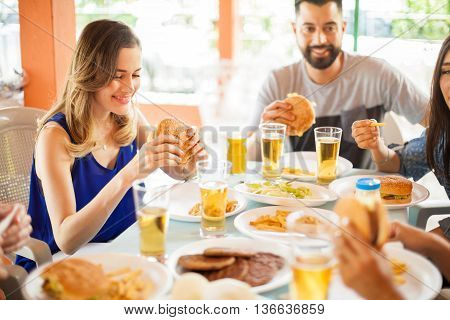 Pretty young woman sitting at a table with her friends eating a cheeseburger at the backyard during a reunion