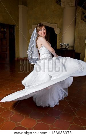 A bride twirls in her wedding dress.
