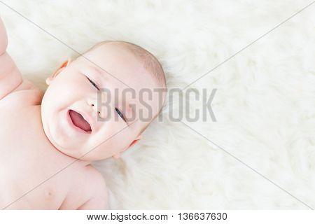 Smiling Baby Lying On Fur