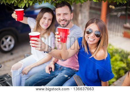 Group of happy friends drinking beer in plastic cups and watching a sports game together at a barbecue