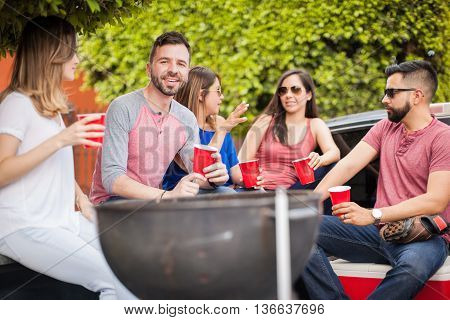 Young Man At A Barbecue With His Friends