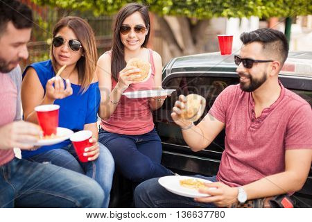 Two young couples wearing sunglasses and eating burgers on a pick up truck on a sunny day in summer