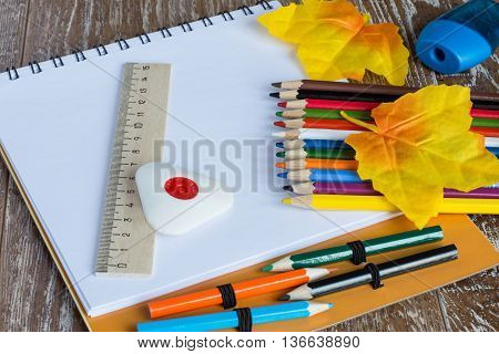 Album for drawing, colored pencils, ruler, eraser and pencil sharpener on a brown wooden background.