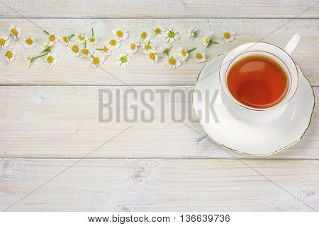 A cup of chamomile tea on the table decorated with chamomile flowers
