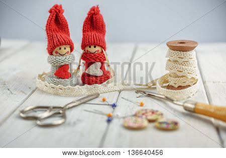 sewing tools like thimble, bobbin lace, pins, scissors, etcetera on wooden background
