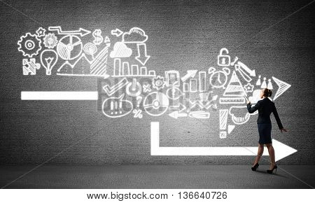 Young elegant businesswoman with flashlight in concrete room