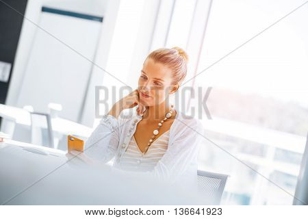 Attractive young woman sitting at desk and using her mobile phone