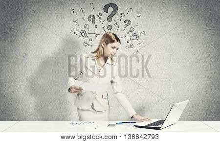 Attractive businesswoman standing at table and using laptop