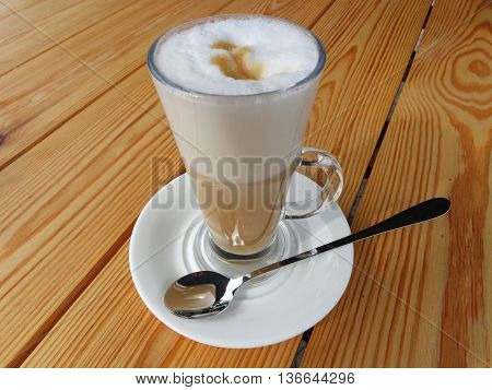 Delicious coffee latte with milk foam and a straw in a glass.The glass stands on a white saucer on an unpainted wooden table.In the saucer lies a brilliant spoon