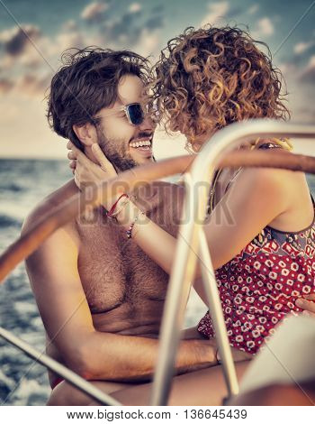 Loving couple on sailboat, two happy lovers kissing and laughing, enjoying romantic date, amazing honeymoon in a sea cruise, active summer vacation