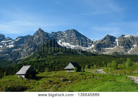 Peaks and two old wooden small huts at trail in Gasienicowa valley in Tatra mountains nearby Zakopane in Poland