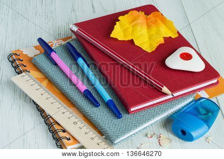 Album for drawing, exercise book, pens, pencil, ruler and eraser on a bright wooden background.
