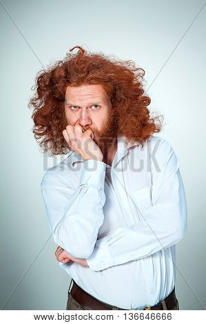 The angry young man with long red hair biting her fingers