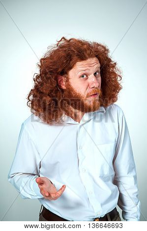 Portrait of young man with long red hair and with shocked facial expression on gray background