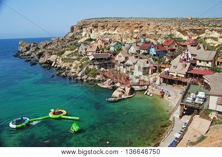 Popeye Village, Malta - September 29, 2013. View over Sweethaven Amusement Park, Anchor Bay and Popeye village in Malta, with people, vintage houses and cliffs in the background.