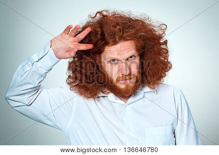 The young man with long red hair looking at camera
