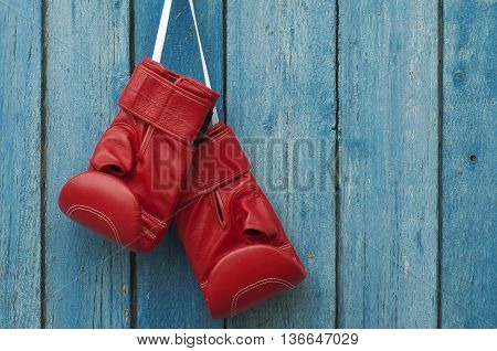 Red pair of boxing gloves hanging in a rustic blue wooden wall
