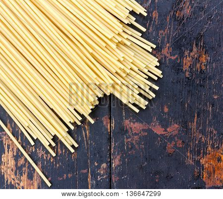 raw spaghetti pasta scattered on black old wooden table close-up view from above