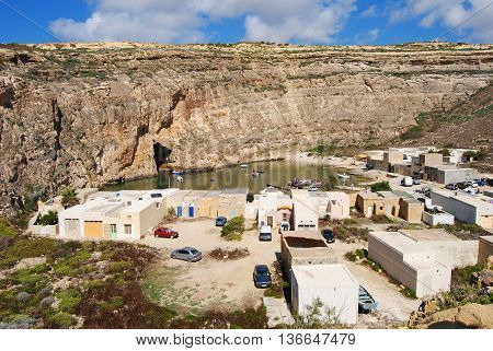 Dwejra, Malta - September 26, 2013. The Inland Sea - a cliff-bound lagoon connected to the open sea by a tunnel that runs for 100m through the headland of Dwejra Point and is big enough for small boats to sail through. With buildings, cars, people and boa