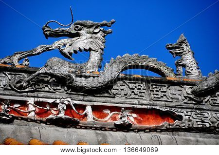 Pengzhou China - October 31 2013: Carved dragon figure sits atop the great hall center roof beam of the Shi Fo Buddhist countryside temple