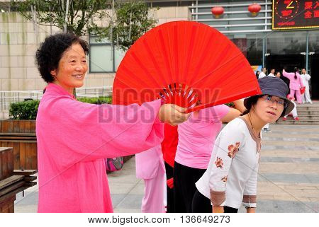 Pengzhou China - October 6 2013: Woman with large red fan practising a Tai 'Chi routine in the Pengzhou Public Library plaza