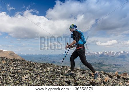 Female running in mountains under sunlight in Altay, Russia