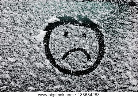 drawn on snow-covered glass face with emotions. Sad