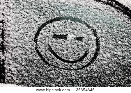 drawn on snow-covered glass smileys with emotions. smiley