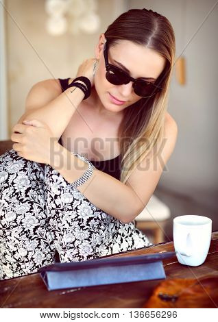Young woman sitting at the outdoors cafe, drinking coffee and reading something at the tablet, enjoying peaceful morning