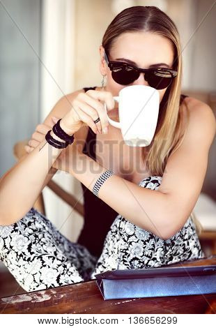 Portrait of a nice happy woman having breakfast outdoors, with pleasure drinking coffee in the cafe, enjoying peaceful morning