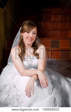 Beautiful bride sitting on stairs in a casual pose with her hands crossed on her knees.