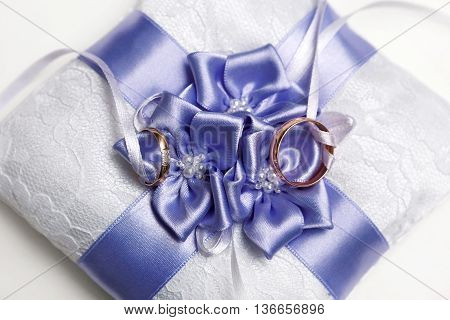 wedding rings on a beautiful pillow with bow