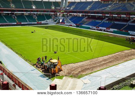 MOSCOW, RUSSIA - MAY 26, 2015: Workers are working on laying and repairing the grass cover at the stadium Locomotive. Field size is 108 and 64 m.