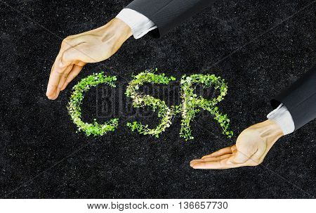 CSR. Small green plants arranged in csr shape with supporting hands on soil background. Corporate social responsibility