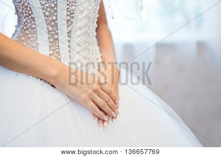 hands of the bride on background of wedding dress